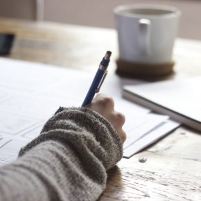 Schreibtisch mit Hand, die einen Stift hält (Foto: Pixabay, CC0)